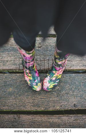 Woman wearing rubber boots, and standing on wet wooden floor outdoor