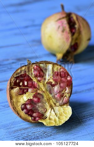 some ripe pomegranate fruits on a blue rustic wooden surface