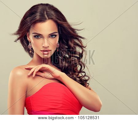 Beautiful model brunette with long curled hair  in coral dress