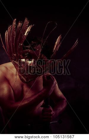 Fighter, warrior with golden mask and huge iron sword, body covered with gold dust