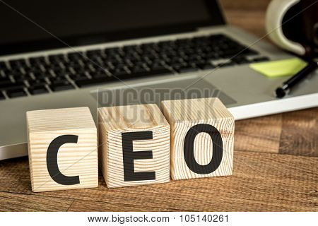 CEO written on a wooden cube in front of a laptop