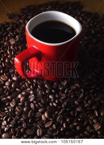 Coffee beans and a red coffee mug