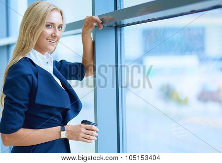 Yound woman drink coffee at office, standing near window