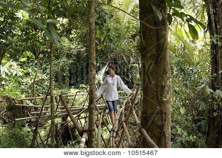 The girl goes on the bamboo bridge.