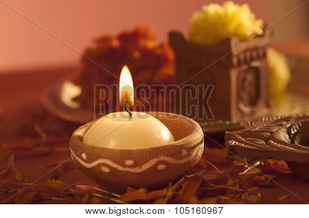 A candle burning in an earthen clay candle holder.