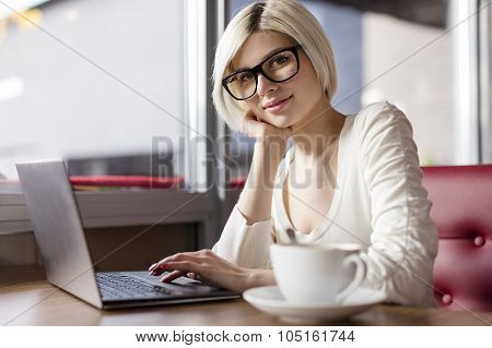 Smiling young woman working with laptop computer in cafe