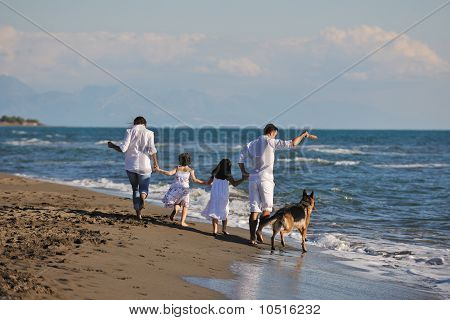 Happy Family Playing With Dog On Beach