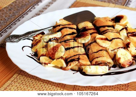 Pancakes stuffed with semolina, bananas and oranges drenched dark chocolate