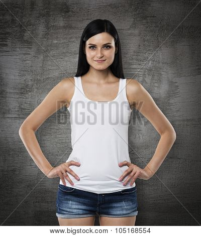 A Brunette Woman In A White Tank Top And Denims. Hands Are In The Pockets. Black Chalk Board On Back