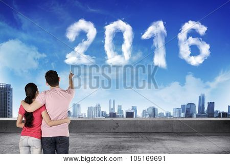 Lovely Couple Pointing To 2016 Cloud Shape On The Sky