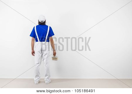 Painter With Paintbrush Looks At White Wall