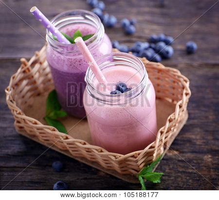 Fresh strawberry and blueberry yogurt on wicker against wooden background