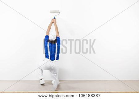Squatting Painter With Paintroller On White Wall