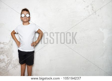 Boy wearing white tshirt, shorts stands on a wall background of  and smiling