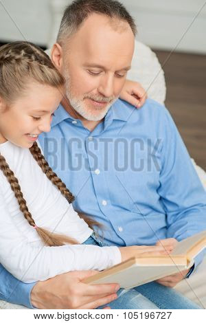 Grandfather with little girl reading book