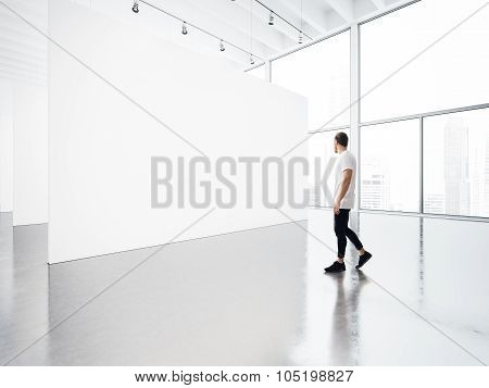 Empty gallery interior with white canvas and young man.