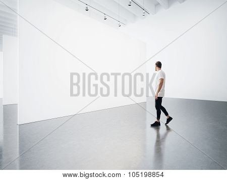 Empty gallery interior with white canvas and man.