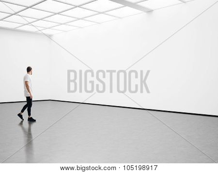 Man walks on the exhibition hall and examines a gallery
