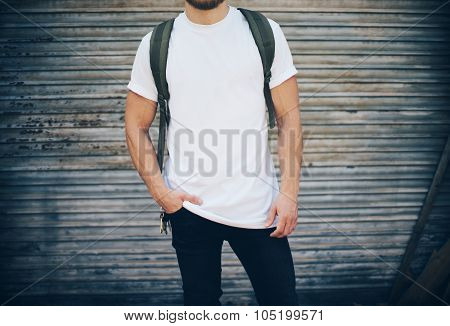 Bearded man wearing white blank t-shirt, blue jeans and green backpack