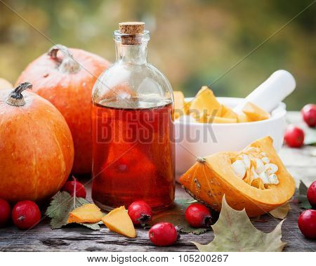 Pumpkin Seeds Oil Bottle, Pumpkins, Hawthorn Berries And Mortar On Wooden Table With Autumn Leaves.