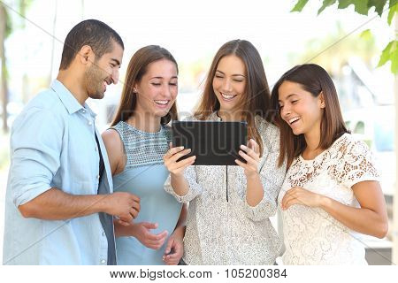 Group Of Four Friends Watching Videos On A Tablet