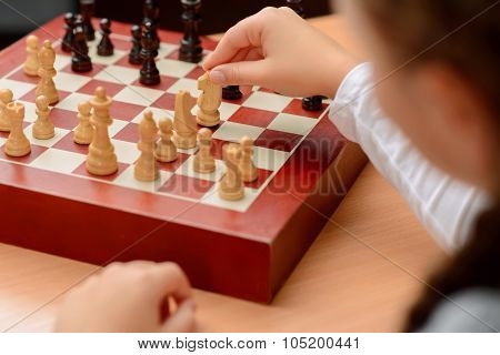 Grandfather playing chess with little girl