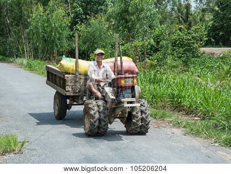 Asian Man Riding Farm Vehicle