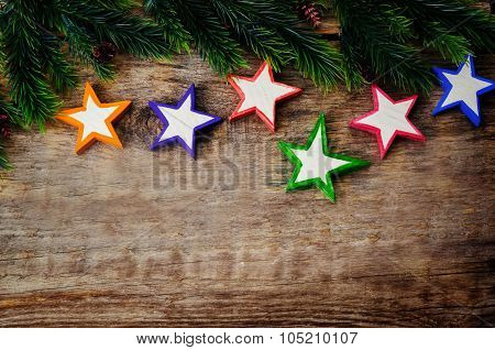 Wooden Background With Wooden Toys In The Shapes Of Stars And The Branches Of The Christmas Tree