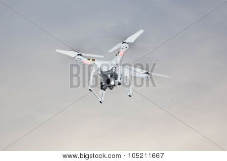 White Drone Hovering In A Bright Grey Sky