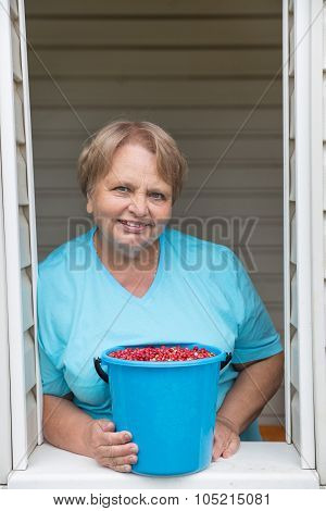 Pensioner woman shows bucket of cowberry