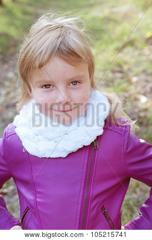 Cute Little Blond Girl In A White Scarf Looking Like A Daredevil. Fall Landscape.