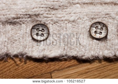 brass buttons on the cardigan on wooden background