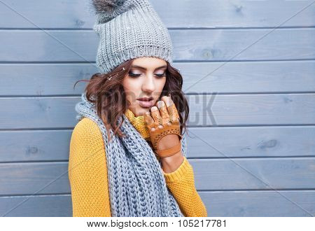 Beautiful natural young brunette woman with eyes closed wearing knitted sweater, leather gloves, scarf and hat. Hair covered with snow flakes. Fall and winter fashion concept.