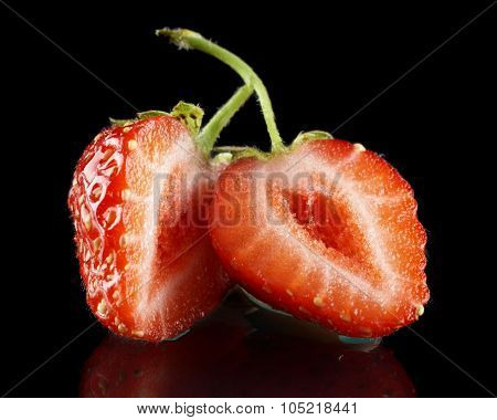 Halved Strawberry Isolated On Black With Green Stalk