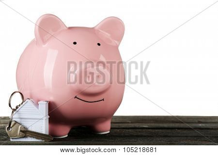 Piggy bank style money box with key on wooden table, isolated on white