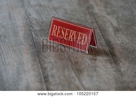 Red Acrylic Reserved Sign On Wooden Table