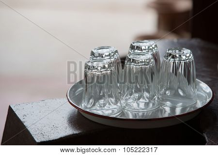 Five Empty Glasses Put Upside Down On White Tray On Wood Table With Natural Light