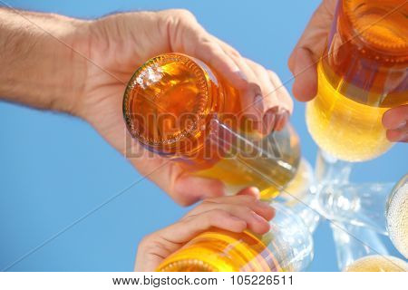 Bottles of beer in people's hands on blue sky background