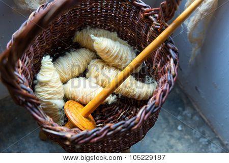 Fresh wool skeins lie in the wooden basket