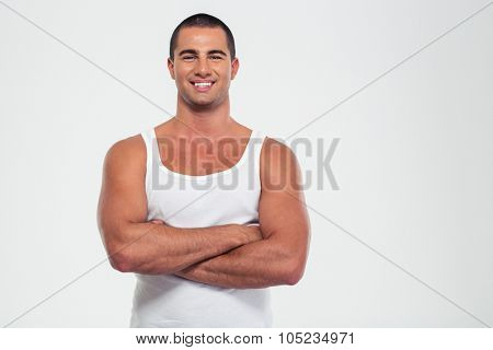 Portrait of a happy muscular man standing with arms folded isolated on a white background