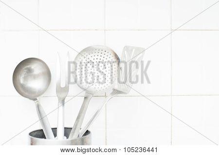 Steel Kitchenwares On White Tile Wall