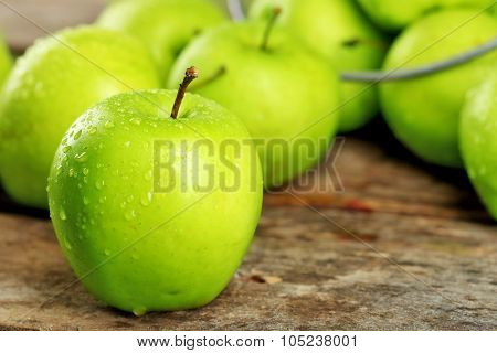 Ripe green apples on wooden table close up
