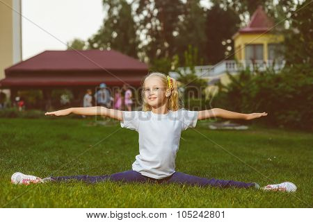 Youthful sportswoman does the splits in a summer park. She is wearing blue  jeans and white shirt