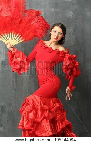 Beautiful dancer in a red dress with a big red fan of feathers in hand