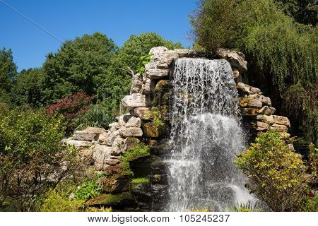 Beautiful man-made waterfall among rocks and trees in summer park.
