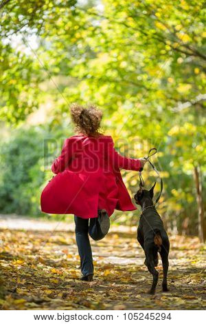 Back view of the woman in a red coat is running with a dobermann in wood.