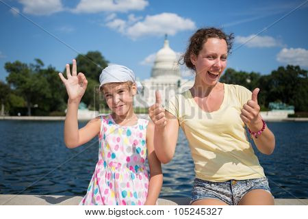 Woman with daughter is showing thumbs up near pond and Capitol at summer.