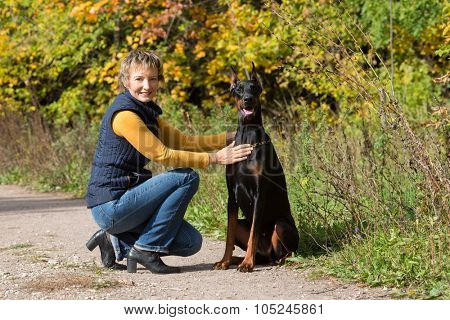 Woman at beige polo-neck is sitting in front of the dobermann in a forest.