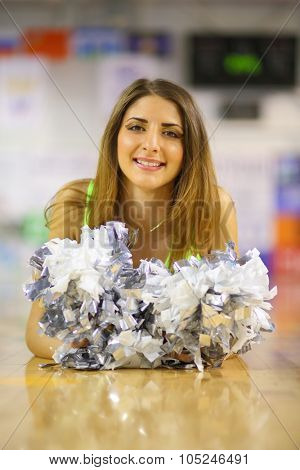 Portrait of girl cheerleader lying on the floor with shiny pompons in the gym