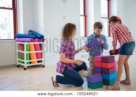 Happy mother with two children play with cubes in light room.